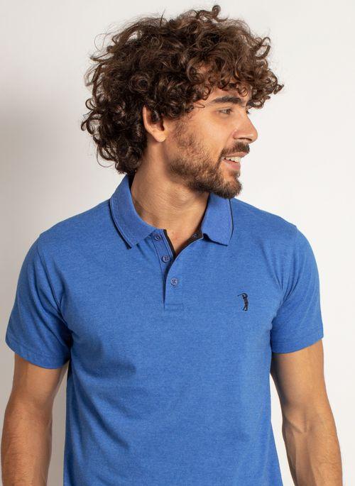 Camisa polo azul combina com short estampado em cores neutras ou com estampa predominantemente no mesmo tom
