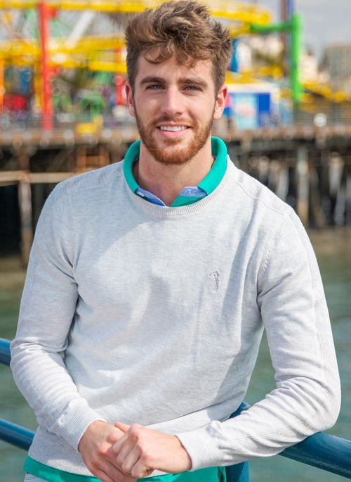 Camisa polo verde se torna um destaque nada previsível em um look com suéter masculino neutro de gola careca