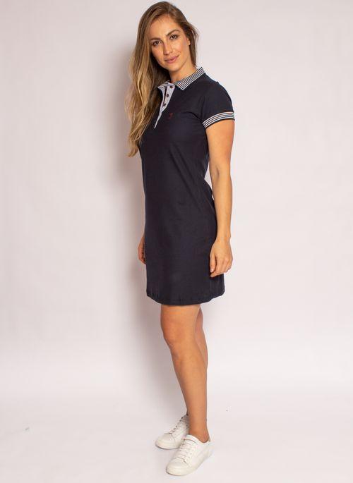 Exemplo de look minimalista feminino  é usar um vestido preto com detalhes em listras branco e preto junto com sapatênis branco